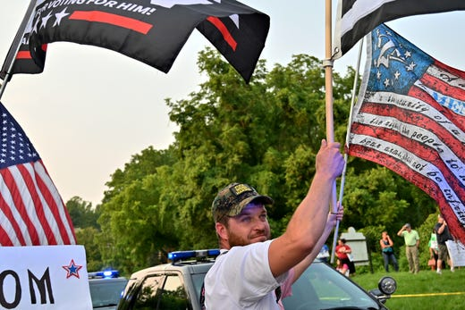 A supporter of former President Donald Trump waves flags on the corner of Delhi Road and Neeb Road outside of Mount Saint Joseph University, where Biden is set to speak at a town hall on Thursday, July 21, 2021.