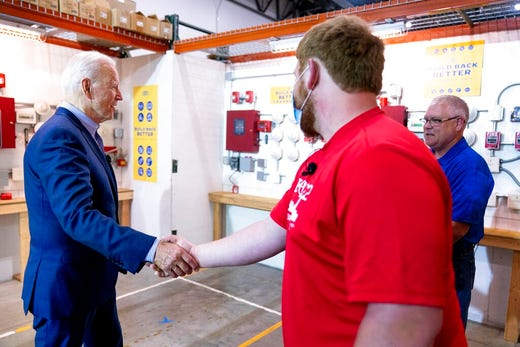 President Joe Biden greets electrician instructor Jerry Mahoney, right, and apprentice Stephen Randolph, second from right, as he arrives to speak with them at the IBEW / NECA Electrical Training Center in Cincinnati, Wednesday, July 21, 2021. (AP Photo/Andrew Harnik)