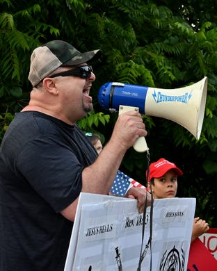 Vince Walsh, of Harrison, shouts to supporters of President Joe Biden on the corner of Delhi Road and Neeb Road outside of Mount Saint Joseph University, where Biden is set to speak at a town hall on Thursday, July 21, 2021.