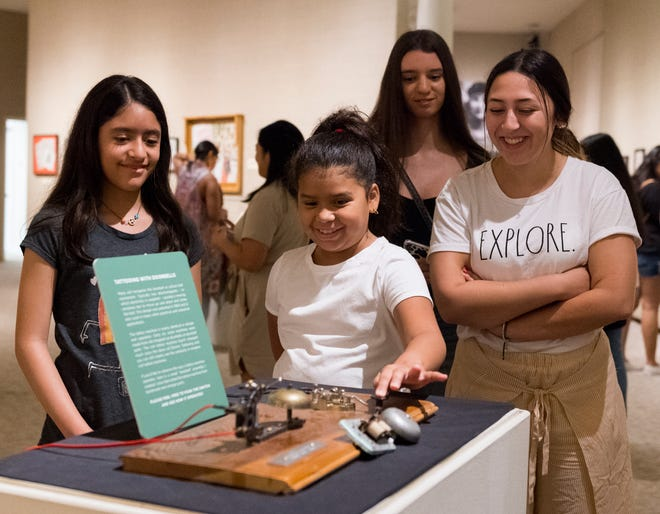 Valerie Macero, left, Katherine García, back, and Daniela Benson Peña, right, watch as Daniela Pinto, center, interacts with an exhibit piece in the Expert Tattooing in the Midwest exhibition at the Evansville Museum of Arts, History & Science during orientation for the Young Girls of Color Leaders Voces En Acción program Wednesday afternoon, July 21, 2021.