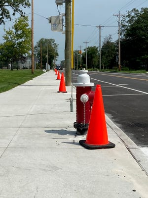 Street cones are shown alongside new sidewalks and fresh road lines in front of the Oak Harbor Middle School.