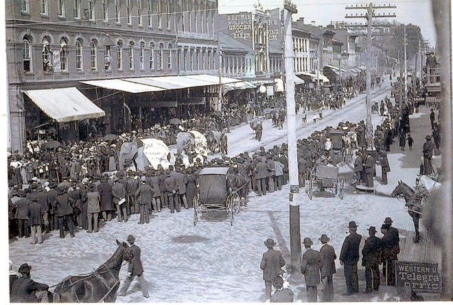 A crowd gathers to watch a circus parade featuring elephants walking west in front of the Rising Block. Circa 1890s.
