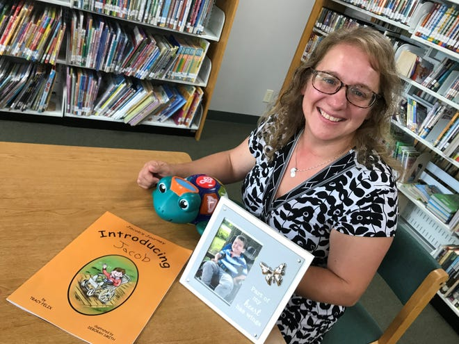 """Children's book author Tracy Felix poses at the Spencer branch of the Marathon County Public Library, with copy of her book, """"Jacob's Journey: Introducing Jacob"""", a picture of her son, Noelie Felix, and Noelie's favorite toy."""