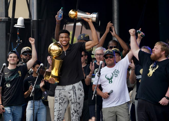Milwaukee Bucks forward Giannis Antetokounmpo (34) holds up his finals MVP trophy while holding the Larry O'Brien trophy as part of the celebration of theMilwaukee Bucks' NBA championship in the downtown Deer District near Fiserv Forum in Milwaukee on Thursday, July 22, 2021.