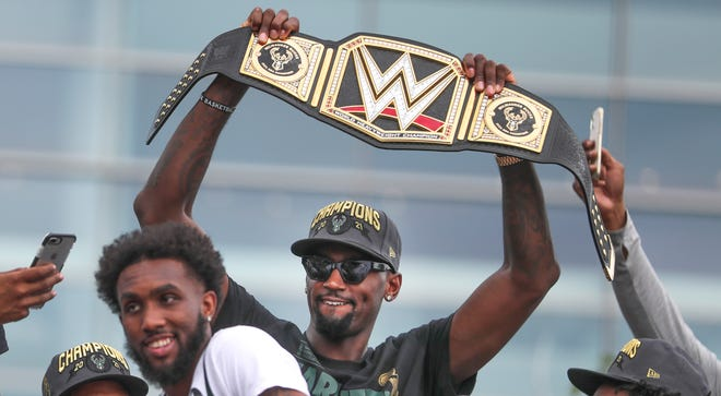 Bobby Portis holds up the Bucks' custom-made WWE championship belt during the team's celebration parade July 22. WWE gifted the title belt to the Bucks to honor the team's NBA championship.
