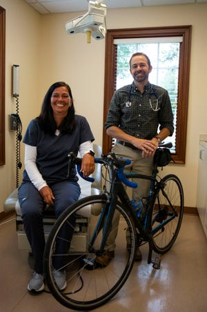 Phlebotomist and Lab Tech Shelly McConnell (left) and Donald DeShetler, M.D., pose inside one of the exam rooms at Cherry Westgate Family Practice - Central Ohio Primary Care with a bicycle as they will both be riding in this year's Pelotonia.