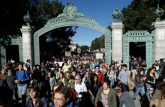 In this Nov. 24, 2014, file photo, students march under Sather Gate during a tuition-hike protest at the University of California in Berkeley.