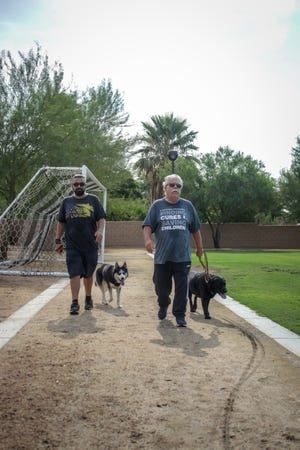 Robert Roach, right, and his service dog Bandit are joined on a morning walk with his son Anthony Roach and his dog Jax around Bagdouma Park in Coachella on July 22, 2021.