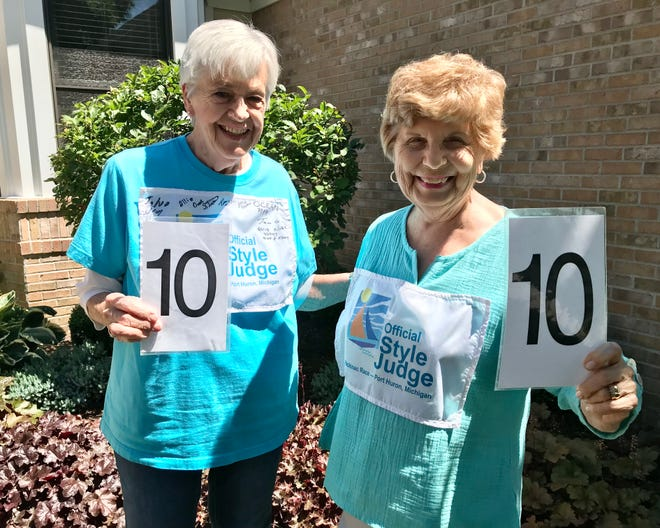 """Port Huron residents and Bayview Mackinac Race """"official style judges"""" Jo Westphal and Joanne Adair hold up score numbers in Port Huron on July 21, 2021."""