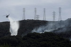 A helicopter drops water near power lines and electrical towers while working at a fire on San Bruno Mountain near Brisbane, Calif.