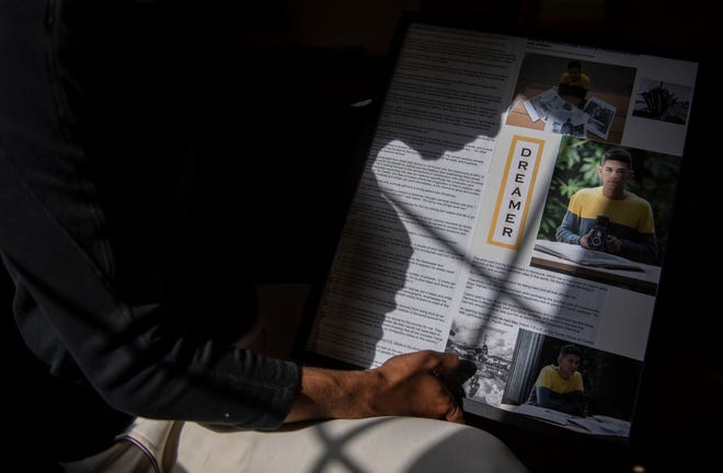 Carlos Rene Castro, holds a picture frame that has photos of him and a written article based on his journey as a Deferred Action for Childhood Arrivals (DACA) recipient inside his home in Salinas, Calif., on Wednesday, July 21, 2021.