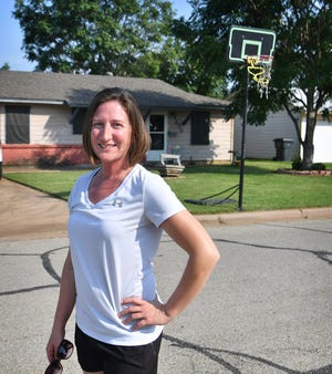 Kari Hill stands in front of her house where a portable basketball goal stands in her front yard. Hill had been issued citations for encroachment, but a judge said the goal can stay.
