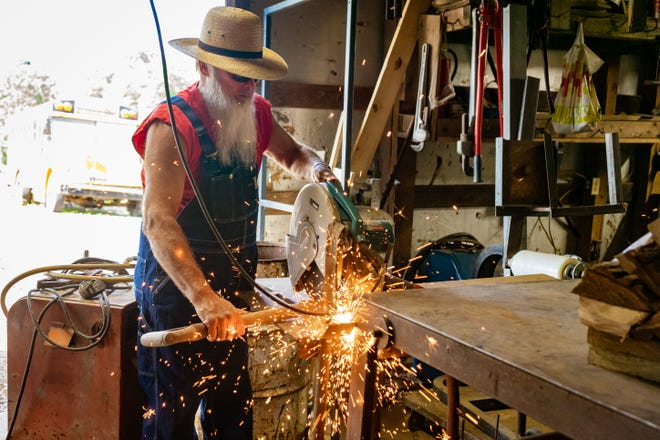 Rick Crooks cuts the handle off a shovel to create body parts for his metal sculptures.