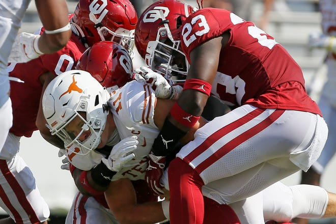 OU's DaShaun White (23) and Delarrin Turner-Yell (32) bring down Texas quarterback Sam Ehlinger during the Sooners' 53-45 win in Dallas last year.