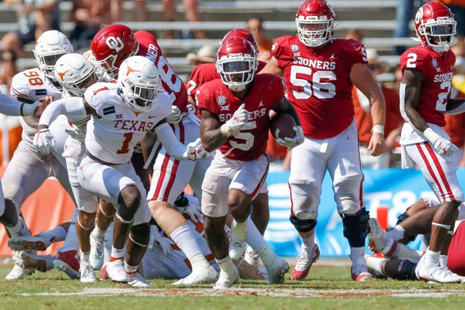 Oklahoma running back T.J. Pledger (5) breaks through the defensive line of Texas Longhorns during the Red River Showdown in 2020.