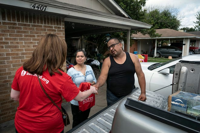"""Austin school district Superintendent Stephanie S. Elizalde, left, visits with Dove Springs parents Araceli Castro and Joel Aguirre during the district's """"Operation Reconnect"""" block walk on June 26. District volunteers canvased areas of Southeast Austin, in hopes of enrolling students in area schools."""