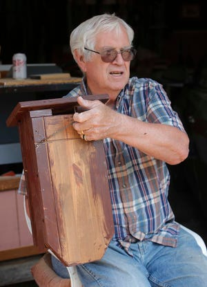 Larry Taylor holds one of the bat houses has has made from repurposed materials  in Stow. Taylor has been asked to build the bat houses for locations around the city.