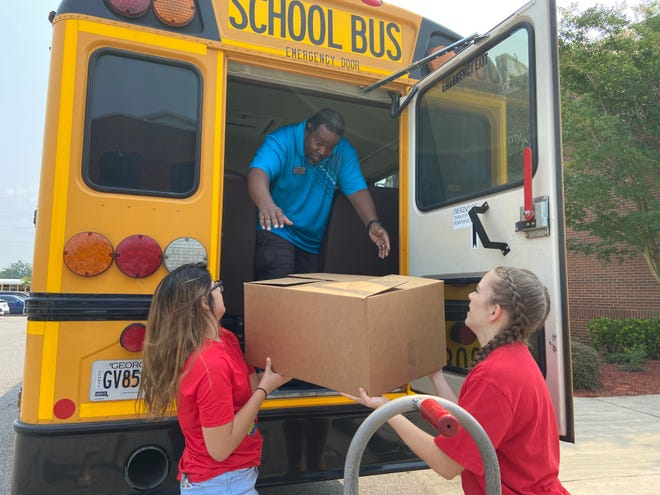 Destiny Galeano and Kelci Walker from AmeriCorps Vista hand a box of school supplies to Columbia County school bus driver Matthew Morrow at the United Way's Stuff the Bus event at the Kroc Center on Friday.