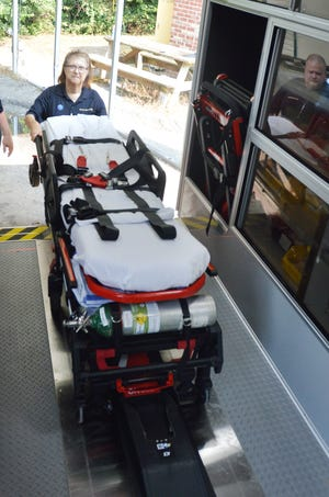 Paramedic Capt. Mary Sasser demonstrates the ease with which she can load and unload patients using the mechanized stretchers on the two new Gold Cross ambulances stationed in Jefferson County.