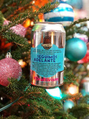 """Prácticas de Provincetown Brewing Company """"el proyecto"""" Donando el 15% de las ganancias a causas progresistas y decidiendo a quién ayudar, como la organización Seguimos Adelante que ayuda a los solicitantes de asilo, sus latas de cerveza."""