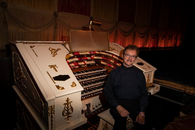 """Organist Clark Wilson next to the Mighty Morton organ at the Ohio Theatre: """"Nobody has more fun in this place than me,"""" Wilson said."""