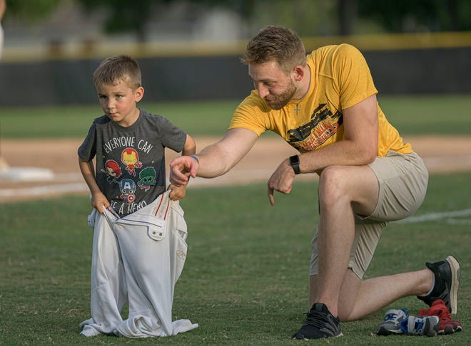 Leesburg Lightning operations intern Colin Budke helps a child during a between-innings contest at Tuesday's game against the Seminole County Snappers at Pat Thomas Stadium-Buddy Lowe Field in Leesburg. [PAUL RYAN / CORRESPONDENT]