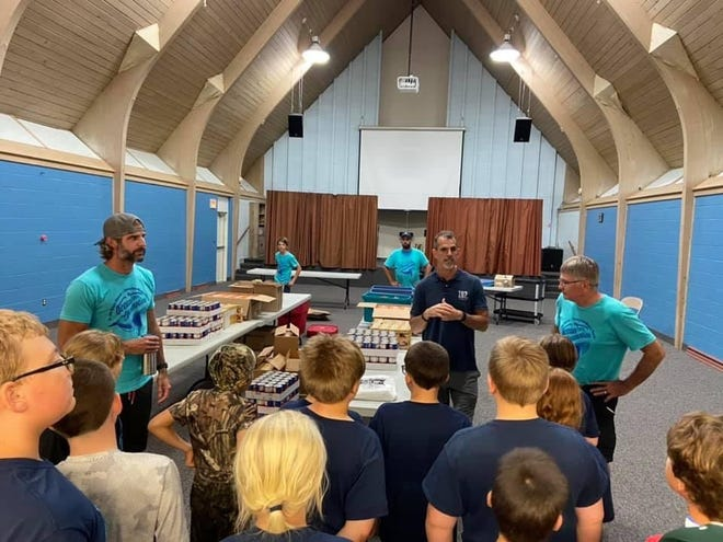 Andy Piatt, center, in blue polo shirt, the founder of I-92 Ministries based out of Clinton, speaks with vacation Bible school participants and leaders during VBS week at the church, July 12-16. The church raised and donated $1,767.06 to I-92 Ministries during Bible school week.