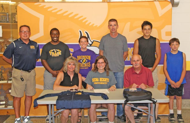 Bronson's Jenna Salek (seated middle) was joined by her family and coaches as she signed her letter of intent to run track and field for Siena Heights University