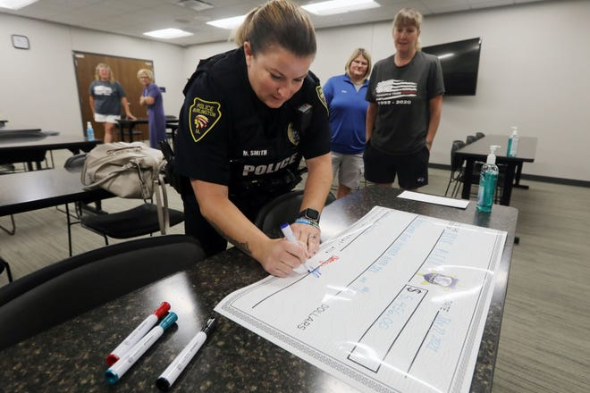 Burlington police officer Melissa Smith signs her name to a giant check being presented to Christy Lister, the Illinois State representative of Blue H.E.L.P., Thursday at the Burlington Police Department.