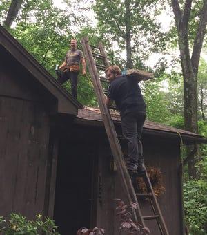 Carole and Gerry Gariepy's son, Cort, waits with a nail gun as Matt Rader brings a bundle of shingles up the ladder.