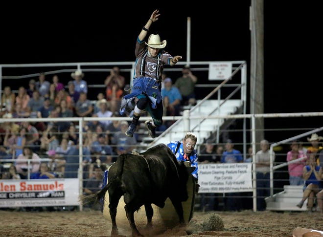 Bullfighter Richard Ratley jumps over a bull with bullfighter Wacey Munsell during the Pretty Prairie Rodeo on Wednesday night.
