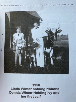 Linda Winter holds ribbons she won at the 1958 Monroe County Fair while her brother, Dennis, holds her first calf and his calf named Ivy.