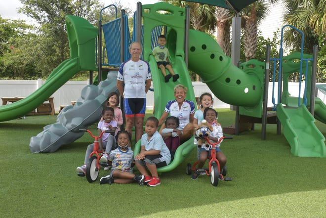 The Opportunists racers Chris Huffman and Kathy Petrillo pose with kids they helped support from the Opportunity School in West Palm Beach. The children of the school followed along online as the Opportunists competed, and even participated in RAAM-based learning during their curriculum.