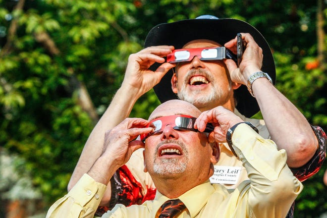Douglas County Commissioner Gary Leif, top, and Judge Ken Madison watch a partial solar eclipse in August 2017 with the help of special glasses from the steps of the Douglas County Courthouse. Leif, 64, died Thursday.