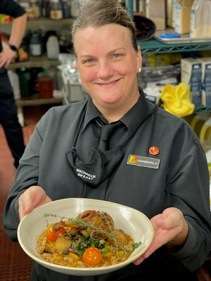 """Kim Lacewell, a server at Michael's on East, sports a """"V is for Vaccine"""" button."""