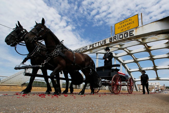 The casket of Rep. John Lewis moves over the Edmund Pettus Bridge by horse drawn carriage during a memorial service for Lewis on July 26, 2020, in Selma, Alabama. Lewis, who carried the struggle against racial discrimination from Southern battlegrounds of the 1960s to the halls of Congress, died July 17, 2020.