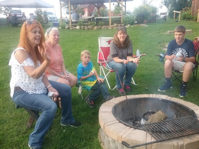 Church of Peace members toast marsh mellows at a recent cookout where about 40 people attended.