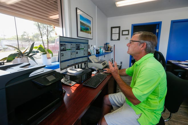 Trent Vausbinder, owner of Trent's Auto World, 109 S.E. 29th St., watches at an online auto auction Friday morning as he tries to find inventory for his lot.