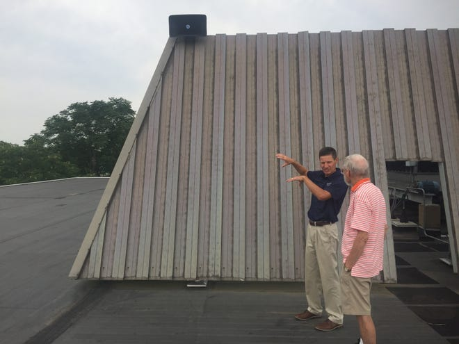 Chad Conrad (left), director of philanthropy for Kent State University of Tuscarawas in New Philadelphia, talks about the new carillon system at the campus with R.J. McCullagh, who donated the system along with his wife, Susan.