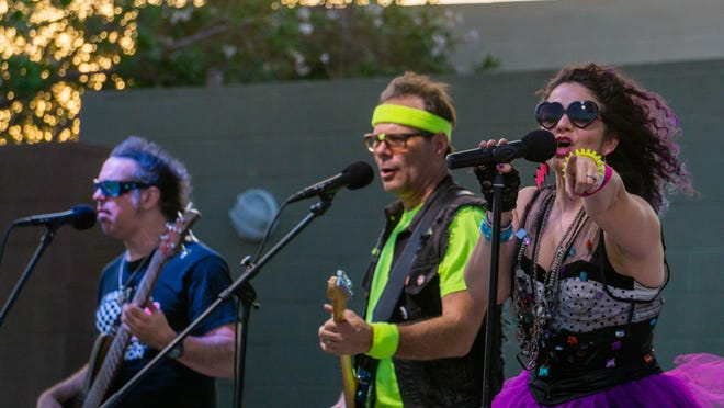 Francesco DiCosmo (left), Paul Byrd and Clarissa Byrd, of the '80s cover group Neon Nation, perform on Thursday, July 22, 2021. The band played the last of the free Sunset Concert Series shows hosted by the town of Apple Valley at Civic Center Park and drew hundreds of fans.