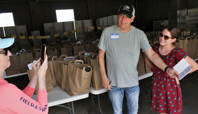 """Wayne Nelson, lead singer of Little River Band, shows off his autograph for Sterling Van Coutren. Sterling's daughter, Reagan, right, got it for him at Highland Food Pantry, where Nelson helped distribute sacks of food items Friday morning. """"He's an old-school rock kind of guy,"""" Van Coutren said of her father."""