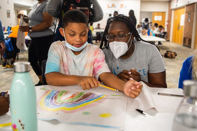 A reader asks if Asheville City Schools and Buncombe County Schools charge teachers $50 to take sick days. In this file photo, ACS teacher Octavia Hamilton helps a student with their daily project at Youth Transformed for Life on Friday, July 23, 2021.