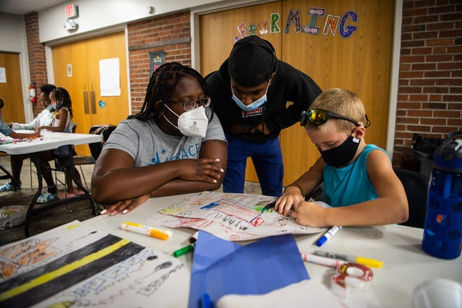 Asheville City Schools teacher Octavia Hamilton helps a student with their daily project at Youth Transformed for Life on Friday, July 23, 2021. Hamilton has been nominated for Cothinkk's Community Leadership Award this year.