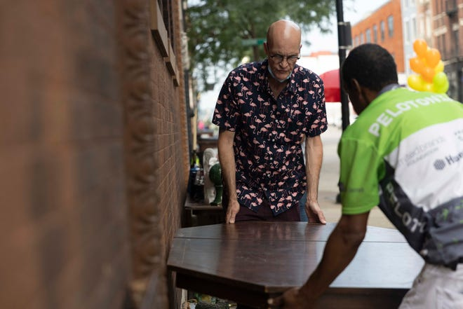 Angelo Young, right, helps Tim Reed, left, move a table during Tim Reed's moving sale, Friday, July 23, 2021, at Court View Apartments at 7 W. Court Street Downtown. Reed, 61, who has lived at Court View for 19 years, faces eviction to make way for a new mixed-use development.