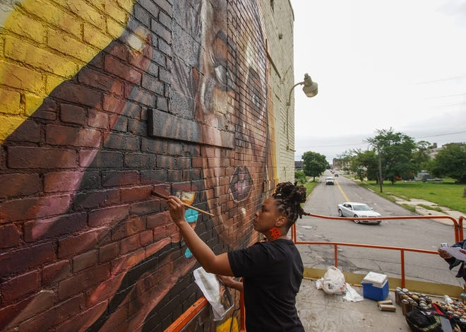 Detroit artist Sydney G. James works on a mural at the intersection of Oakland Avenue and Clay Street in Detroit on Friday, July 23, 2021 as part of the all Black produced BLKOUT Walls Mural Festival. The event, that was conceived by Detroit artist Sydney G. James, Thomas Evans (Detour303) of Denver, Colorado and Max Sansing of Chicago, will feature 24 large scale murals.