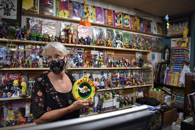 Susan Bonner holds a customer-made replica of the old Halley's Comics sign Thursday, July 22, 2021 in Fort Collins, Colorado. Bonner and her husband, John, opened the Walnut Street shop in February 1988. After 33 years, they're closing up shop and retiring.