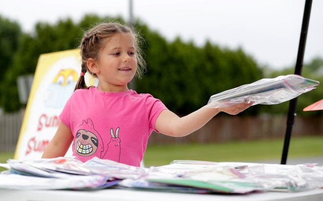 Mae Bulkowski, 6, smiles after choosing a selection of books at the Sunny Summer Readers pickup location on July 22, 2021, at De Pere Middle School.