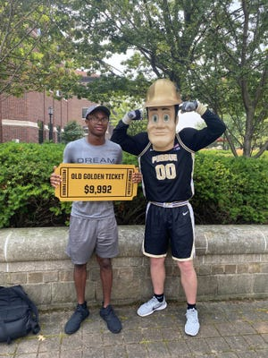 Quentin Betts standing with Purdue Pete in celebration of his Old Golden Ticket win on July 23, 2021.