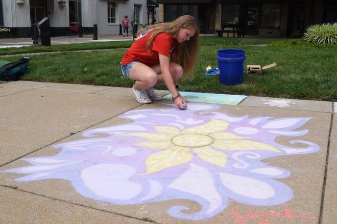 Sarah Scott, una studentessa della Fairfield Christian Academy, lavora su un'opera d'arte ispirata al film Disney Tangled nel centro di Lancaster venerdì 23 luglio 2021.