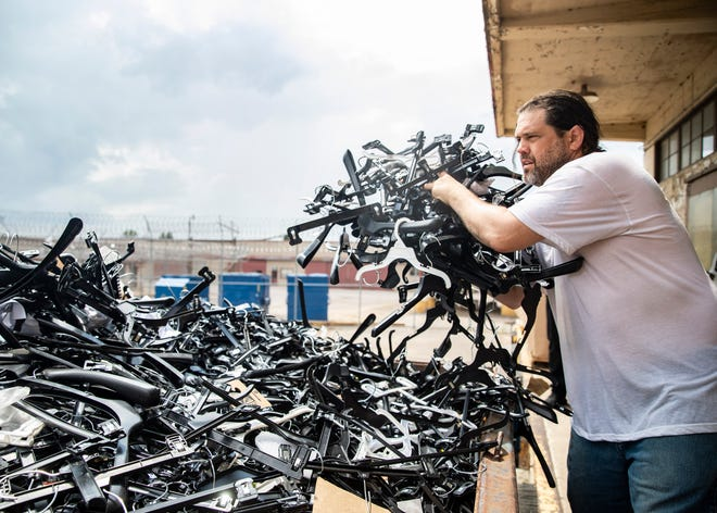 William Strohm tosses broken hangers into a trash pile at the Shelby County Corrections Department in Memphis, Tenn., on Friday July 23, 2021. The hangers are assorted and repaired and shipped back to retail companies for use.
